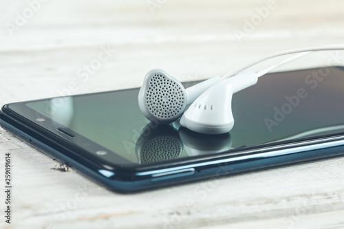 earphone on phone on desk - 259891614