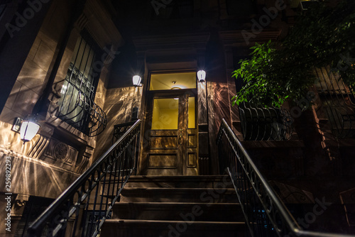 Old typical houses at night in Harlem, in New York City, USA
