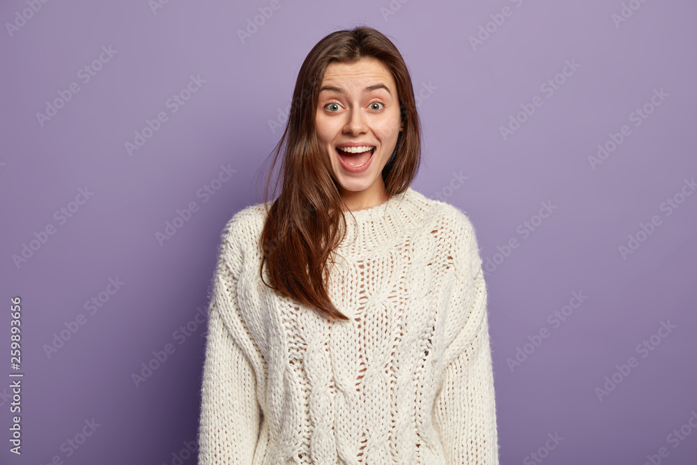 Fototapety, obrazy: Positive young female with glad expression, opens mouth from surprise, reacts on positive unexpected news, wears white jumper, stands against violet studio wall, intrigued by telling something