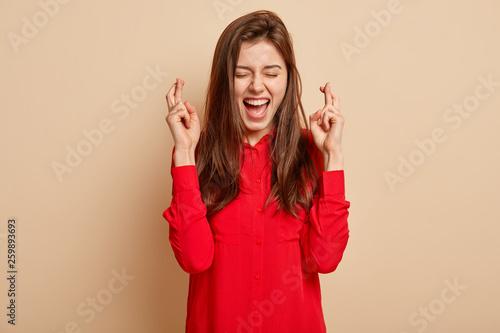 Photo of overjoyed lovely dark haired female crosses fingers