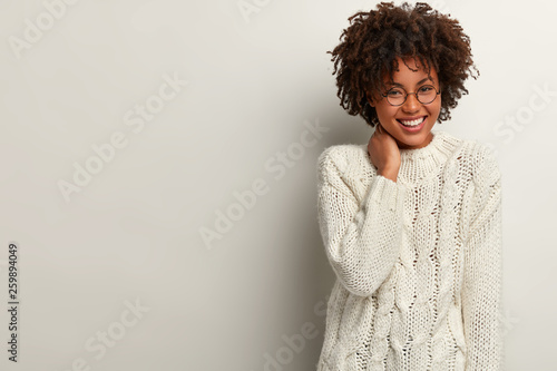 Obraz na plátně Glad laughing curly woman giggles as heard funny joke, wears white sweater, keeps hand on neck, expresses positive emotions, stands indoor, blank space right for your advertisement