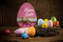 Colorful Painted Happy Easter Greeting Card Eggs In Birds Nest Basket On Rustic Wooden Background
