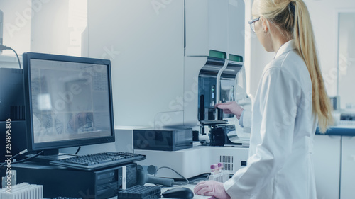 Photo  Female Research Scientist Working with Medical Analyzing Machine for Testing Tubes with Blood Sample
