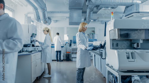 Team of Research Scientists Working On Computer, with Medical Equipment, Analyzing Blood and Genetic Material Samples with Special Machines in the Modern Laboratory Canvas Print