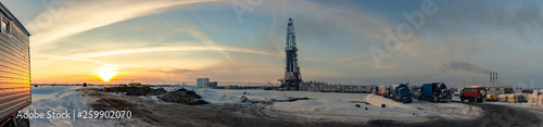 drilling rig on land in winter in the cold against the sunset and the beautiful sky panorama