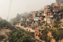 Poor Area Of Haridwar, India. House Poor People On The Hillside In Front Of A Dirty River. Social Problems Of Our Time