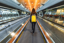 One Woman Traveller With Backpack Go On Moving Walkway Travolator In New Hamad International Airport. Back View