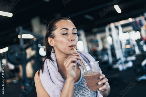 Young attractive woman after successful workout in modern fitness gym holding glass of protein shake and drinks with drinking straw.