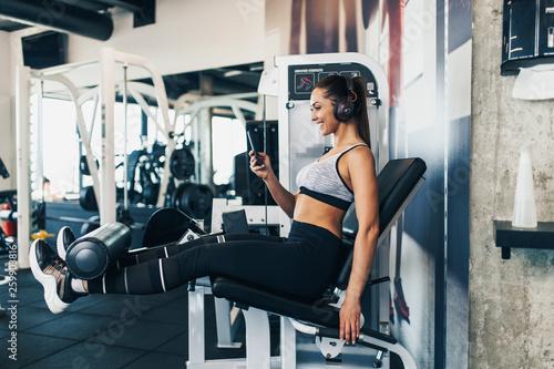Młody pasuje i atrakcyjna kobieta pracuje w nowoczesnej siłowni i słuchania muzyki w słuchawkach bluetooth i smartfonie.