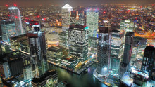 Aerial Drone Night Shot From Iconic Canary Wharf Illuminated Skyscrapers Business And Financial Area, Docklands, Isle Of Dogs, London, United Kingdom