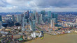 Aerial drone shot from iconic Canary Wharf skyscraper business and financial area with lots of clouds, Docklands, Isle of Dogs, London, United Kingdom