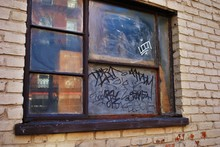 Close Up Of A Broken Boarded Up Window And Sill With Peeling Paint And Graffiti