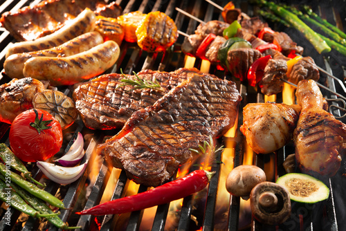Canvas Print Delicious grilled meat with vegetables sizzling over the coals on barbecue