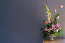 Fake Flowers In A Vase On Wood Table With Gray Background