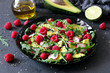 Avocado salad with raspberries, pomegranate, arugula and sesame on dark background. Top view with copy space. Vegetarian and vegan food.