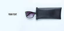 Sunglasses With Protective Leather Case On Gray Background. Copy Space.