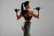 Fitness woman doing exercise with dumbbells on gray background. Muscular woman workout, rear view