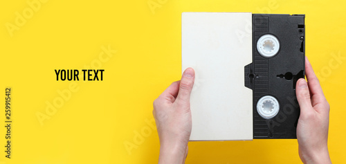 Vászonkép  Woman hands holding videocassette in cover, videotape on a yellow background with copy space for your text