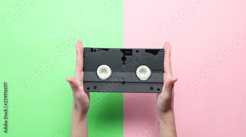 Valokuvatapetti Female hands holds video cassette on pink green pastel background