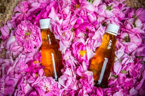rose water bottles inside a basket of rose petals Tableau sur Toile