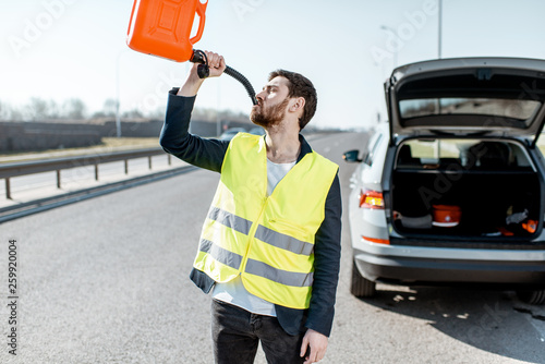 Fotografie, Obraz  Funny portrait of a man drinking from the refuel can near the broken car on the