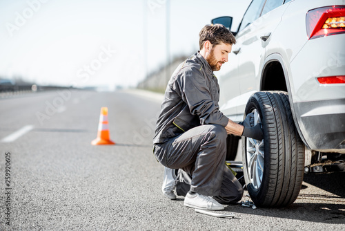 Handsome road assistance worker in uniform changing car wheel on the highway Canvas Print