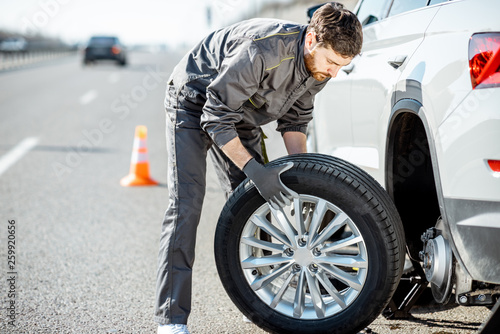 Valokuva  Handsome road assistance worker in uniform changing car wheel on the highway
