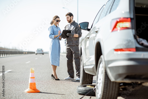 Fotografía Road assistance worker signing some documents with woman near the broken car on