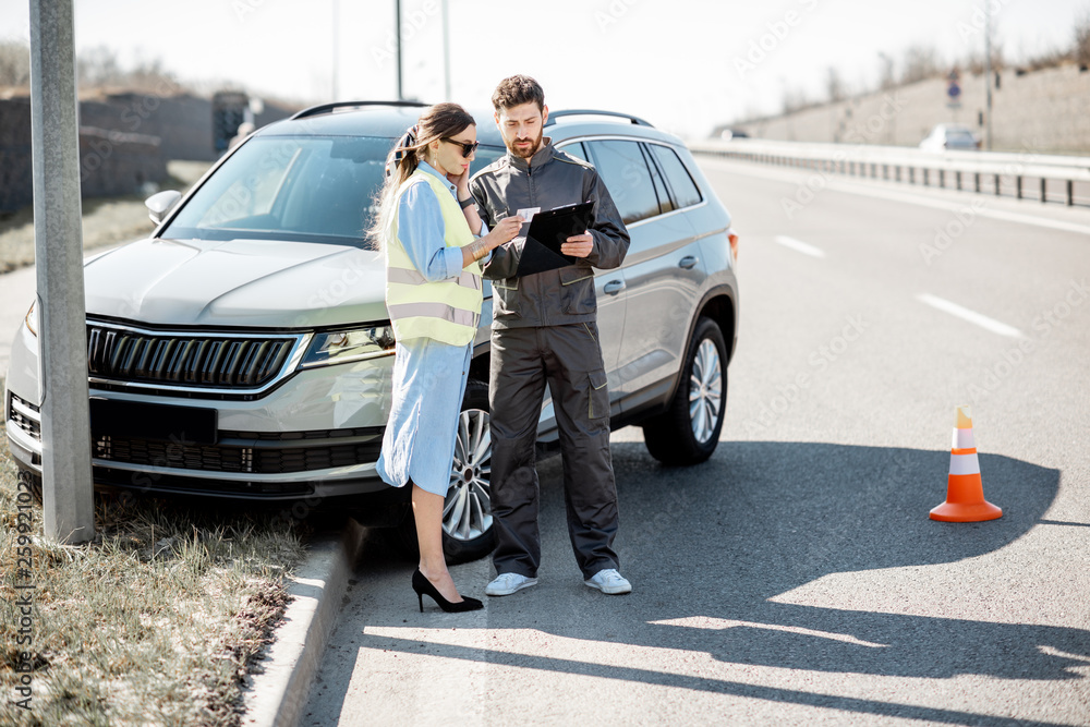 Fototapety, obrazy: Woman with road assistance worker signing some documents standing near the car in road accident on the highway