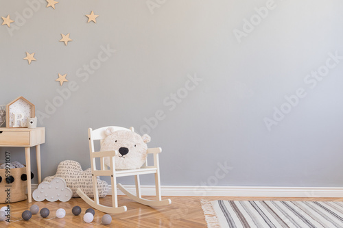Obraz Stylish scandinavian newborn baby room with toys, children's chair, natural basket with teddy bear and small shelf. Modern interior with grey background walls, wooden parquet and stars pattern. - fototapety do salonu