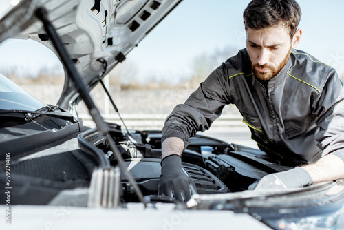 Photo Handsome auto mechanic or road assistance worker in uniform repairing engine of