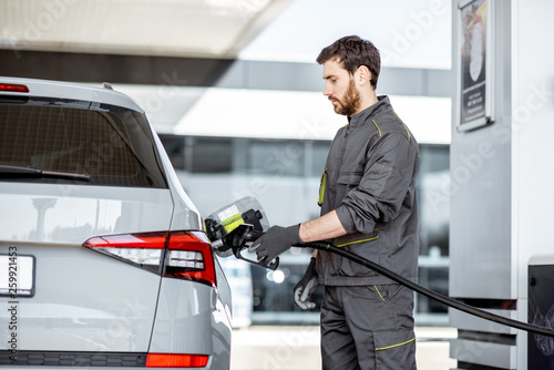 Valokuvatapetti Gas station worker in workwear refueling luxury car with gasoline holding fillin