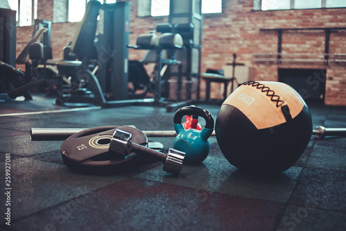 Fotografie, Obraz  Disassembled barbell, medicine ball, kettlebell, dumbbell lying on floor in gym
