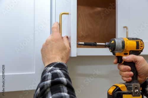 Photo The installing a furniture handle process of assembling cabinet