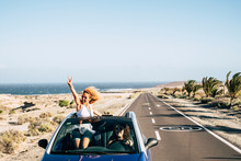 Happy Cheerful Couple Of Young Caucasian Crazy Woman With Curly Hair Enjoy The Travel And Vacation Staying Outside The Roof Of A Convertible Car With Long Road And Ocean In Background - Joyful