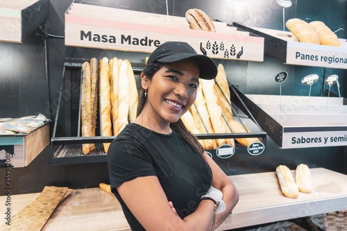 Fotografiet Beautiful latin woman serving bread in pastry shop.