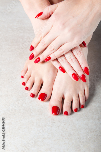 Fototapeta Young lady is showing her red manicure and pedicure nails