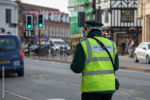 Photo civil enforcement officer or traffic warden walks up the street whilst writing a