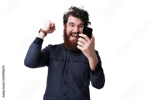Fotomural  Portrait of a happy young bearded mann isolated over white background, holding m