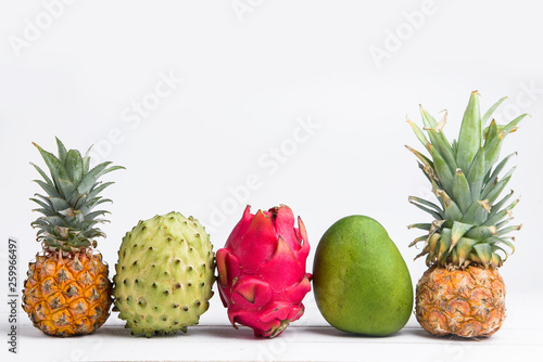 Exotic fresh summer fruits on white background. Dragon fruit, pineapple, persimmon, mango, annona cherimola flat lay with free copy space. - 259966497