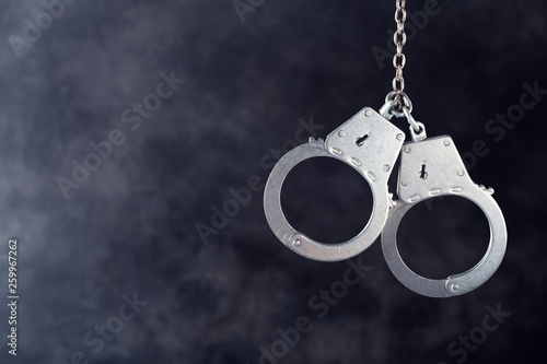 Handcuffs hanging against a dark background with copy space Wallpaper Mural