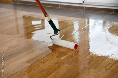 Cuadros en Lienzo Lacquering wood floors. Worker uses a roller to coating floors.