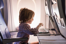 5 Year Old Boy On Airplane, Using  A Laptop