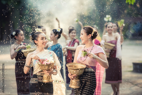Leinwand Poster Vientiane Laos APRIL 4 2019 : Young happy beauty Asian woman splashing water during  Water Songkran festival ,Thailand Laos traditional
