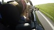 Slow motion footage of beagle sitting on lap in convertible car