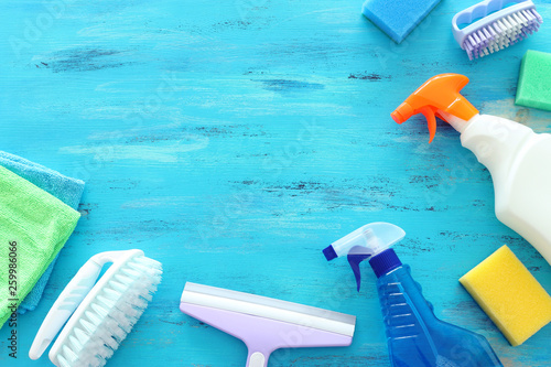 Obraz na plátně  Spring cleaning concept with supplies over wooden background