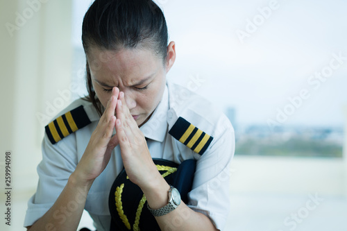 Photo Stressed out female pilot worried at work.
