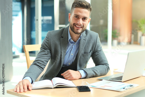 Foto Portrait of happy businessman sitting at office desk, looking at camera, smiling