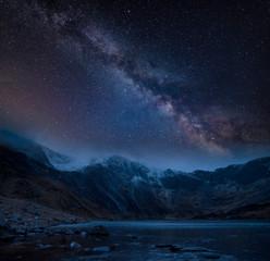 Złożony wizerunek zima krajobraz snowcapped pasmo górskie przy nocą z Milky sposobem above