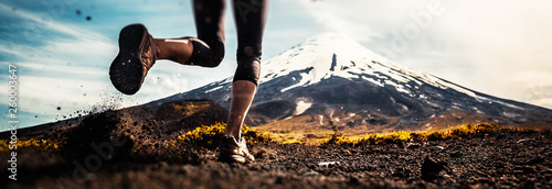 Fotografía  Legs of the woman running on the trail with volcano on the background